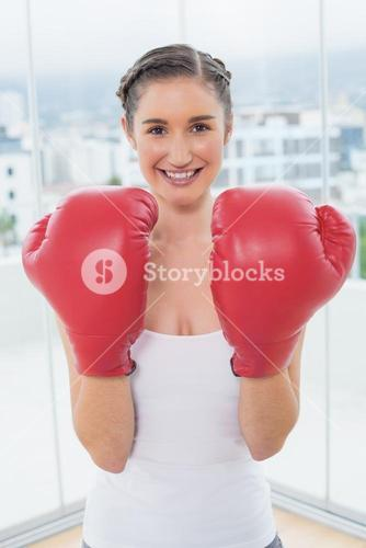 Cheerful sporty brunette wearing boxing gloves