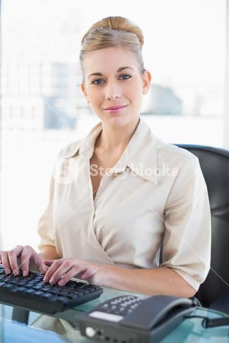 Stylish young blonde businesswoman typing on her keyboard