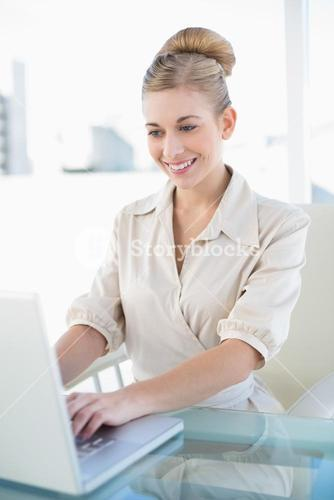 Stylish young blonde businesswoman using a laptop