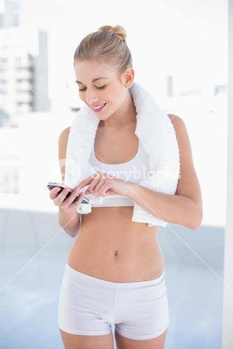 Content young blonde model texting on her mobile phone