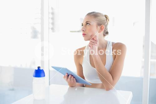 Pensive young blonde model using a tablet pc
