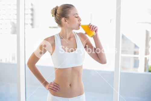 Peaceful young blonde model enjoying orange juice