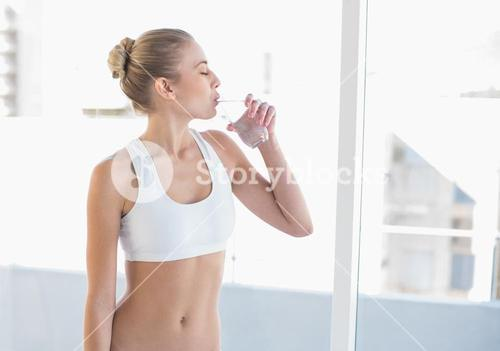 Peaceful young blonde model drinking water