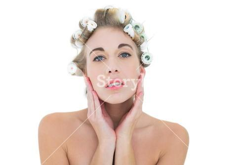 Thinking blonde model in hair curlers holding her head