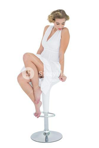 Pensive fashion blonde model posing with closed eyes on bar chair