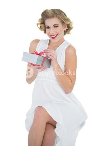 Delighted fashion blonde model opening a gift