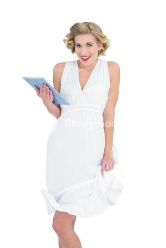 Amused fashion blonde model holding a tablet pc
