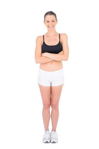 Smiling woman in sportswear crossing arms looking at camera