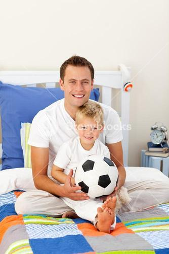Portrait of a little boy and his father playing with a soccer ball