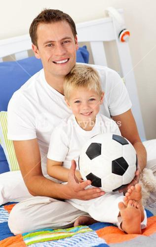 Close up of a little boy and his father playing with a soccer ball