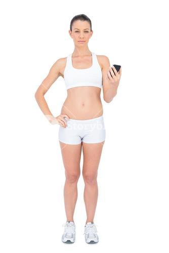 Serious woman in sportswear holding smartphone