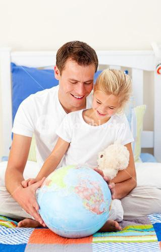 Earing father and his daugther looking at a terrestrial globe