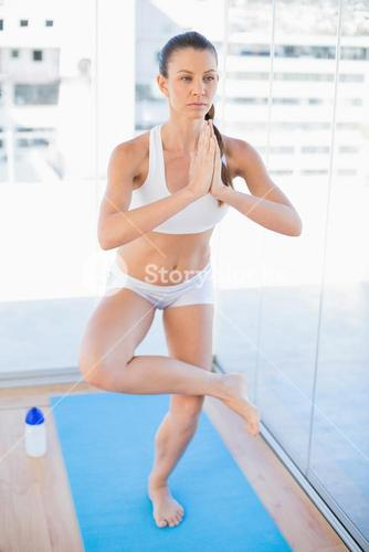 Concentrated fit woman practicing yoga