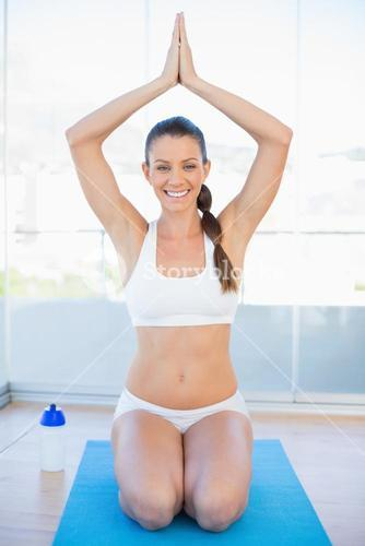 Smiling sporty woman sitting in yoga position on exercise mat