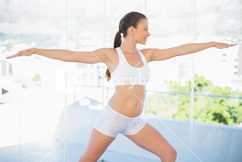 Smiling fit woman stretching in yoga warrior pose