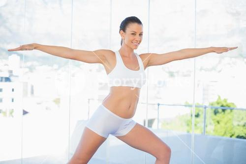 Cheerful fit woman stretching in yoga warrior pose