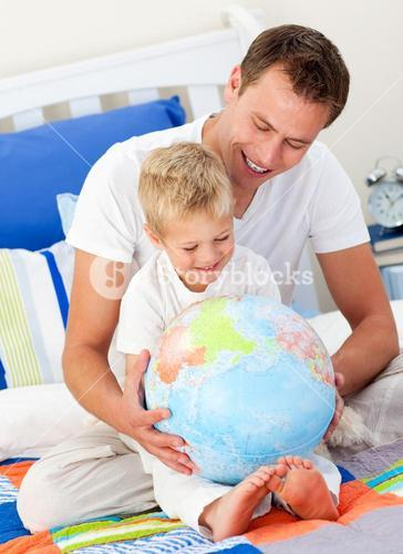 Merry father and his son looking at a terrestrial globe