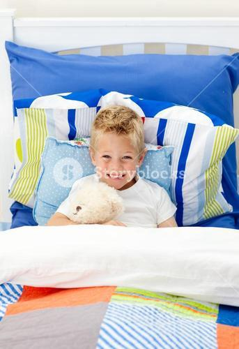 Cute little boy lying in bed