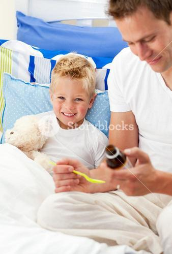 Smiling father giving cough syrup to his sick son