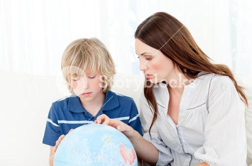 Captivated child looking at a terrestrial globe with his mother