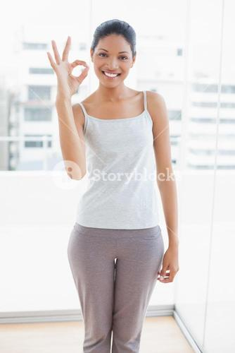 Cheerful sporty young woman making okay gesture