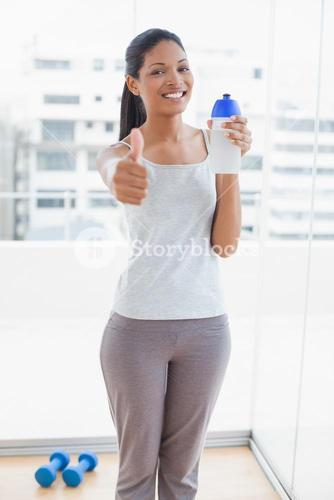 Smiling sporty young woman giving thumbs up