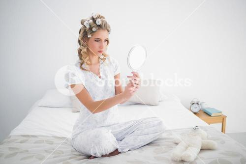 Serious blonde looking at reflection on cosy bed