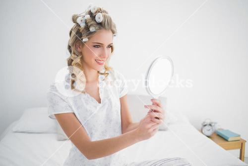 Smiling blonde looking at reflection on cosy bed