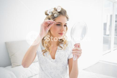 Peaceful natural blonde using tweezers on her eyebrow