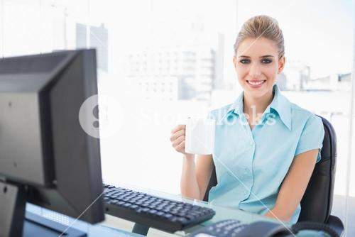 Smiling well dressed businesswoman holding coffee
