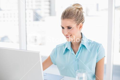 Cheerful well dressed businesswoman using laptop