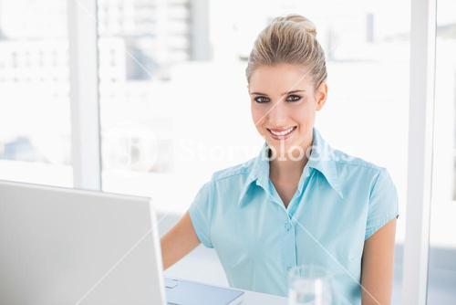 Smiling well dressed businesswoman using laptop