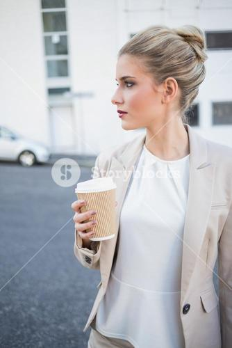 Peaceful stylish businesswoman holding coffee