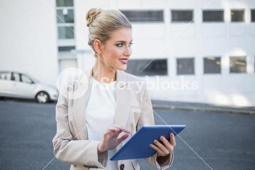 Cheerful stylish businesswoman using digital tablet