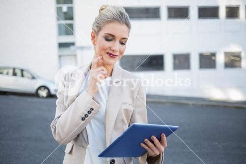 Pensive stylish businesswoman using digital tablet