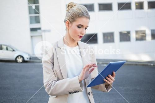 Serious stylish businesswoman scrolling on digital tablet