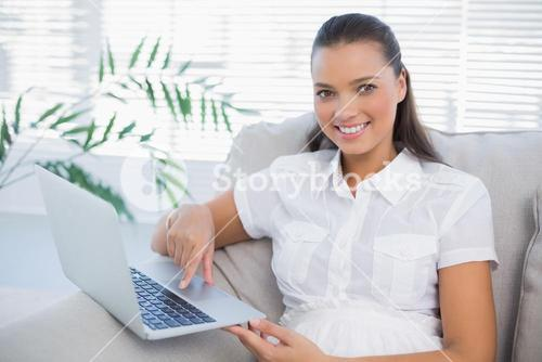 Smiling pretty woman using laptop sitting on cosy sofa