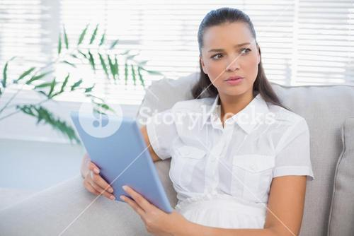 Thoughtful cute woman using tablet sitting on cosy sofa