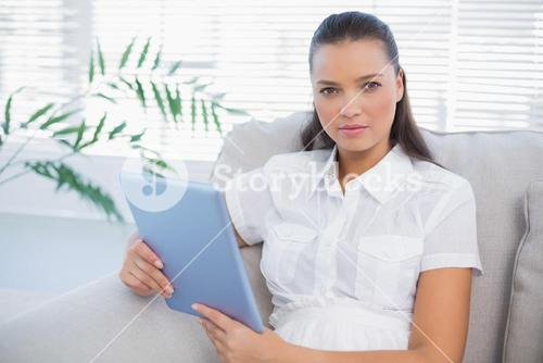 Serious cute woman holding tablet sitting on cosy sofa