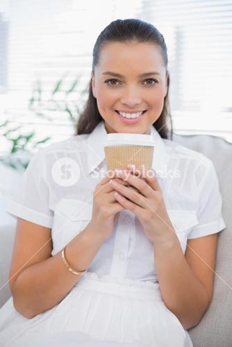 Smiling pretty woman having coffee sitting on cosy couch