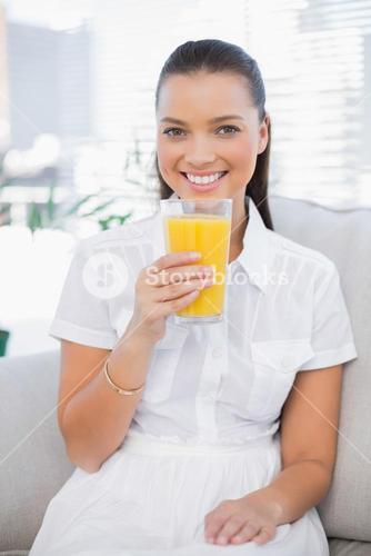 Smiling pretty woman holding orange juice sitting on cosy couch