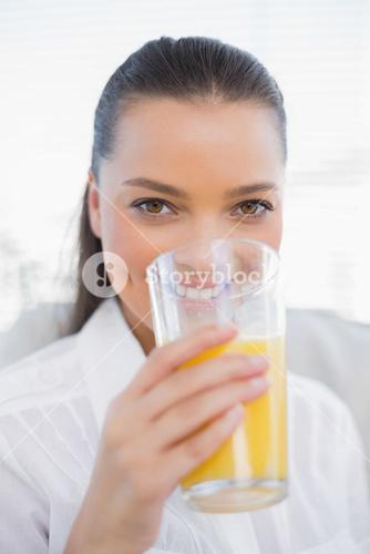 Smiling pretty woman drinking orange juice sitting on cosy couch