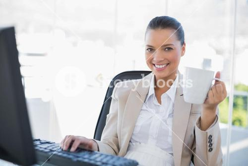 Smiling sophisticated businesswoman holding coffee