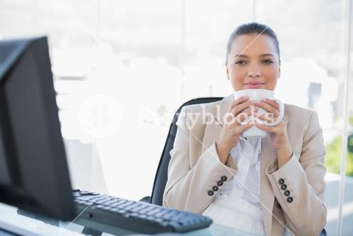 Relaxed sophisticated businesswoman smelling coffee