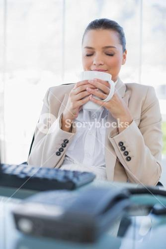 Peaceful sophisticated businesswoman smelling coffee