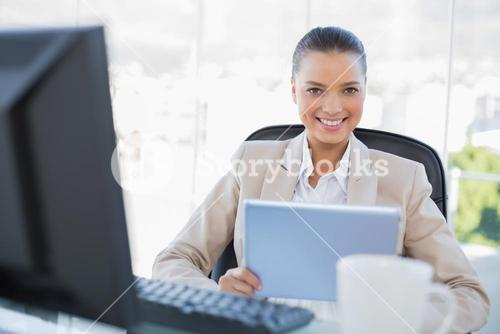 Smiling sophisticated businesswoman holding tablet pc
