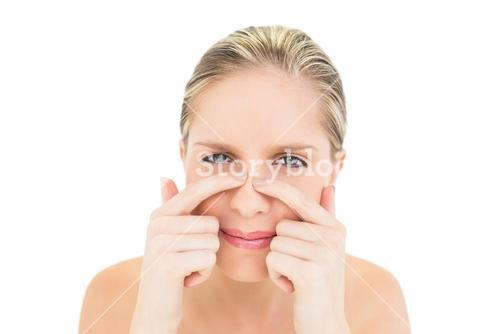 Frowning fresh blonde woman pressing her nose