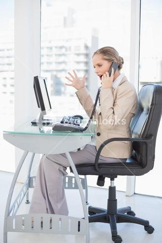 Angry blonde businesswoman on the phone