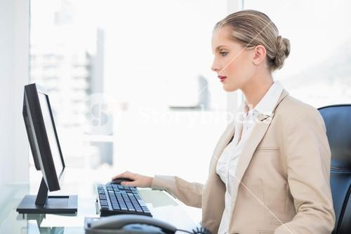 Peaceful blonde businesswoman working on computer
