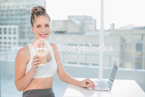 Smiling sporty blonde using laptop holding coffee